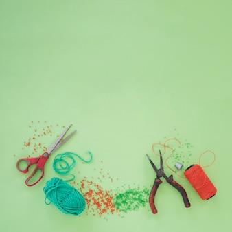 Tesoura; alicate; lã; grânulos e um carretel de fio laranja sobre fundo verde