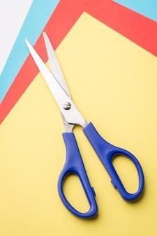 Tesoura azul em papéis coloridos. modelagem com papel