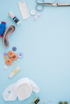 Tesoura; botões; agulhas; carretel; fita métrica; fita no pano de fundo azul