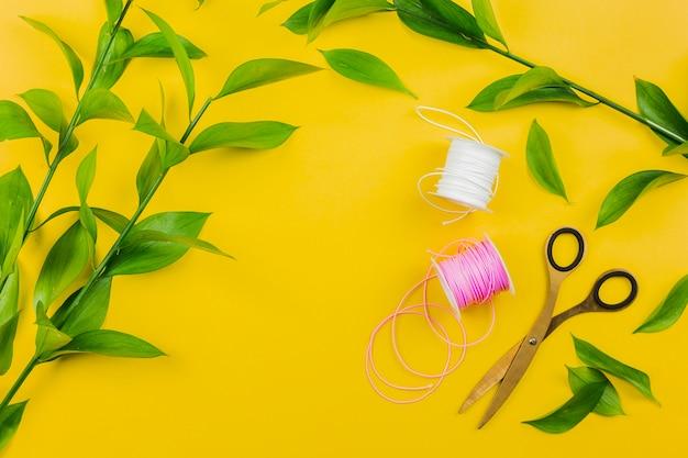 Tesoura; carretel de fio branco e rosa com galho de folhas verdes em fundo amarelo