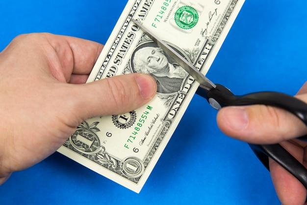 Tesoura corta um dólar.
