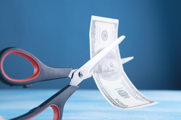 Tesoura corta uma nota de dólar pela metade