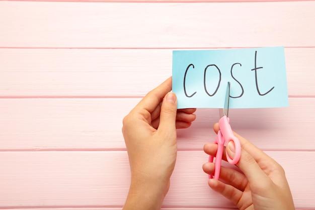 Tesoura cortando o conceito de custos de palavra para recessão ou crise de crédito.