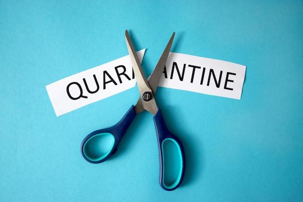 Tesoura cortando um pedaço de papel com a palavra quarentena. símbolo do fim de covid-19. de volta à vida normal. futuro pós-pandemia ou restrições de quarentena relaxantes. após o bloqueio do coronavírus