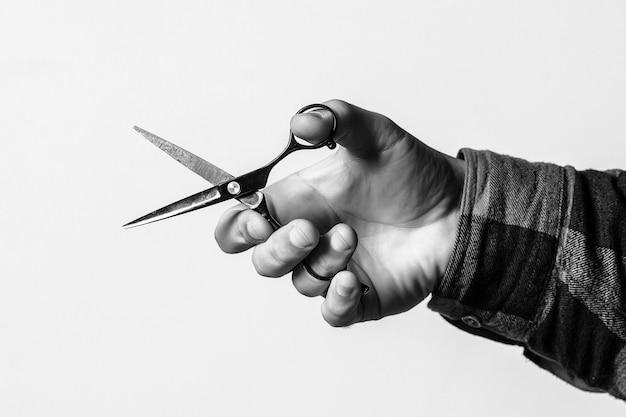Tesoura de barbeiro com espaço de cópia. barbearia. cabeleireiro mão segura uma tesoura, imagem recortada.