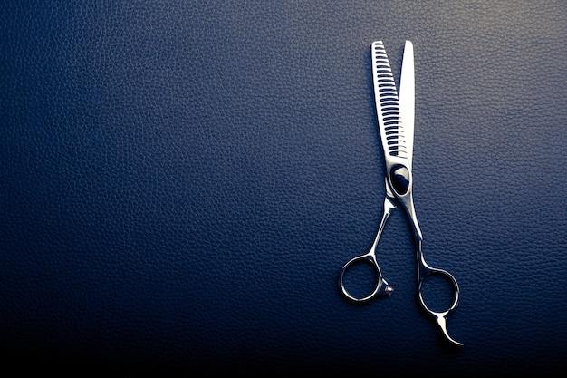 Tesoura de cabeleireiro em fundo de couro preto com espaço de cópia
