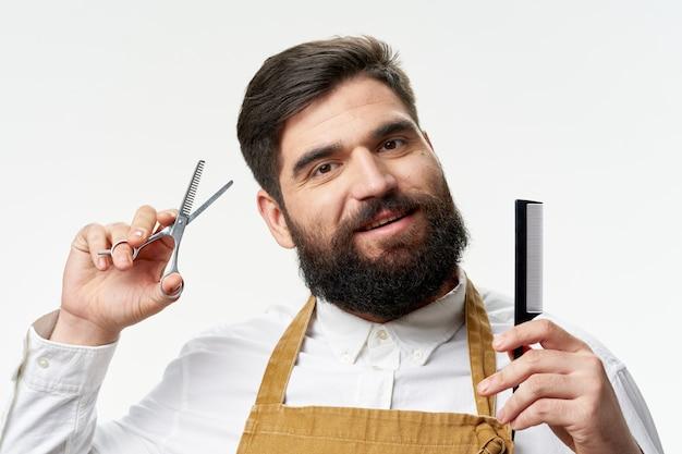 Tesoura de corte de cabelo profissional de barbearia e pente nas mãos de um avental de homem