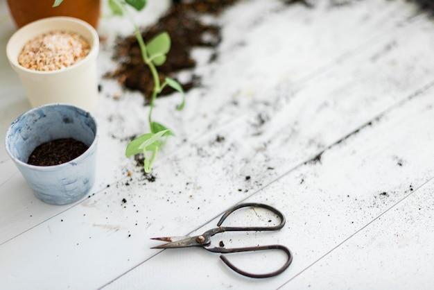Tesoura de jardinagem faça você mesmo em uma mesa suja com vasos de plantas