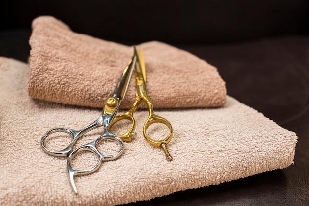 Tesoura de ouro e prata colocada em toalhas