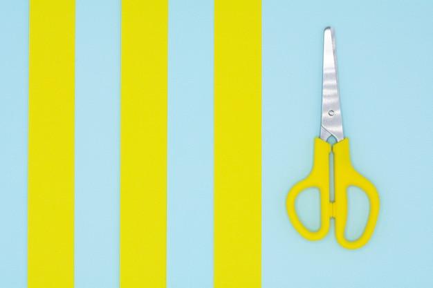 Tesoura de plástico amarela sobre fundo azul e amarelo