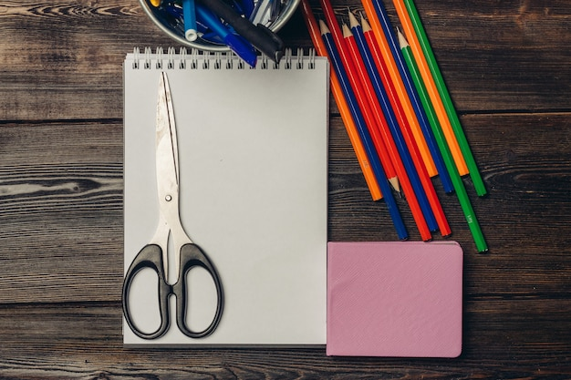Tesoura deitada em um caderno aberto e lápis de cor em uma vista de mesa de madeira