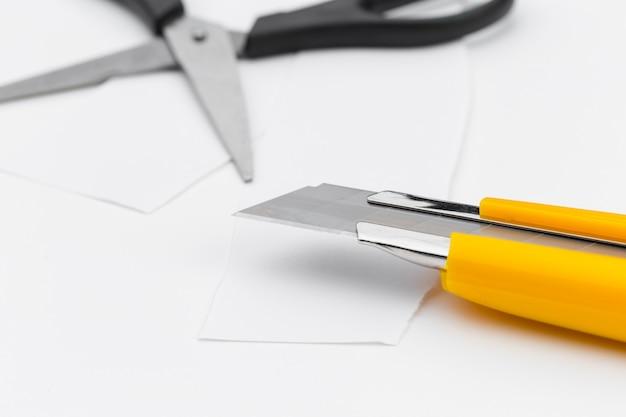 Tesoura e faca de papel em um fundo branco