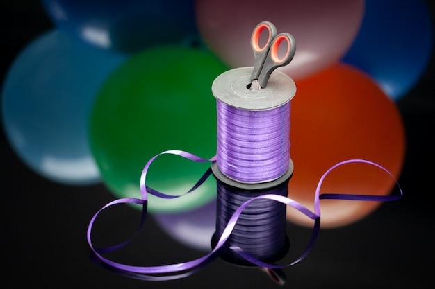 Tesoura e fita washi roxo no fundo borrado balões multicoloridos.