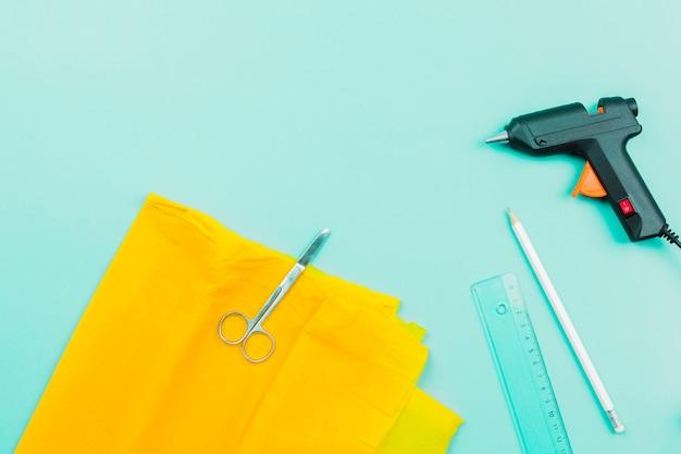 Tesoura em papel amarelo; régua; lápis e pistola de cola elétrica em fundo turquesa