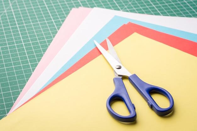 Tesoura em uma pilha de papéis coloridos diferentes