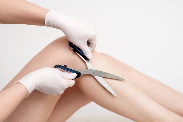 Tesoura nas mãos de mulher cortando cabelo nas pernas. conceito de depilação.
