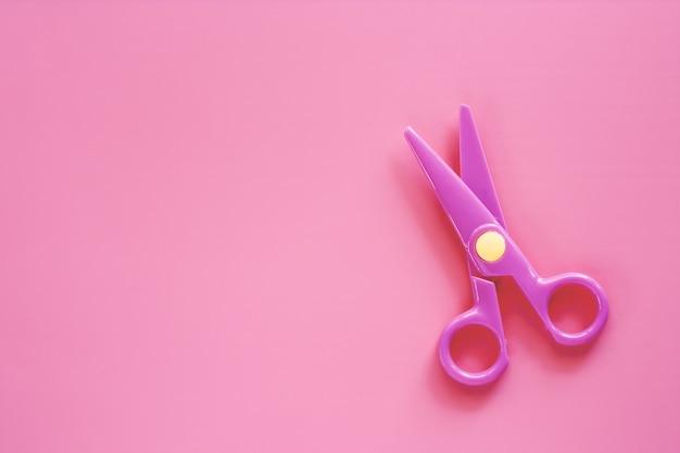 Tesoura no fundo rosa com espaço de cópia para o objeto de escritório e escola estacionária