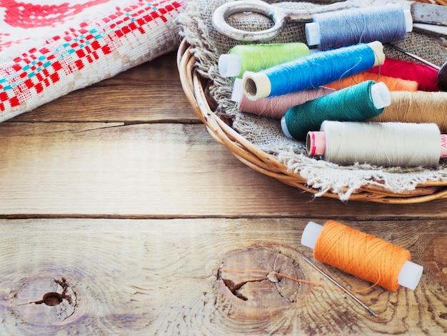 Tesouras, bobinas com fios e agulhas, tecido listrado. ferramentas de costura antigas na superfície de madeira velha.