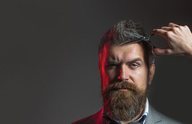 Tesouras de barbeiro. homem barbudo, barba exuberante, bonito. hipster na barbearia. corte de cabelo de homem na barbearia. barbearia vintage, barbear-se. homem barbudo, barba longa, brutal, homem caucasiano com bigode.
