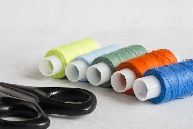 Tesouras e bobinas de alfaiate com fios coloridos