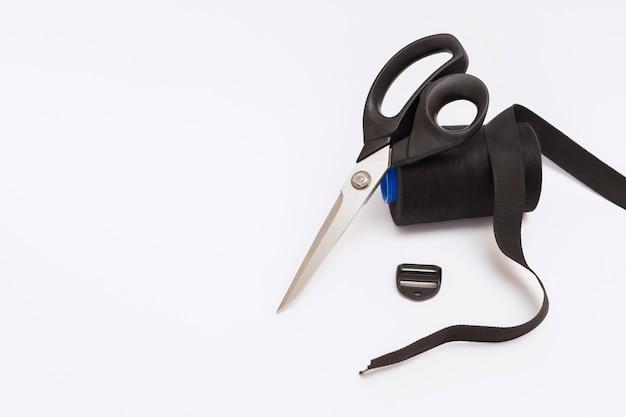 Tesouras e fios para costura em um fundo branco e isolado. espaço livre para texto