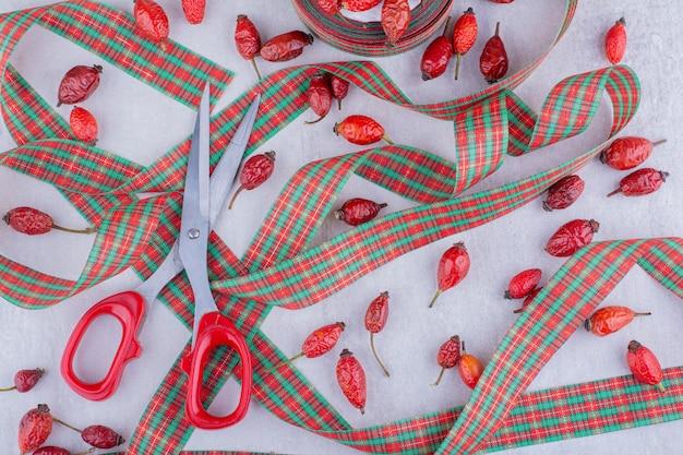 Tesouras, fitas coloridas de doces de natal e frutas de rosa de cachorro em fundo branco.