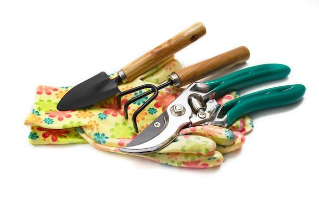 Tesouras, luvas, ancinho e pá de ferramentas de jardim isolam em um fundo branco. o conceito de jardinagem, agricultura, agricultura de quintal. cuide do jardim. agricultura, agricultura, conceito de jardinagem