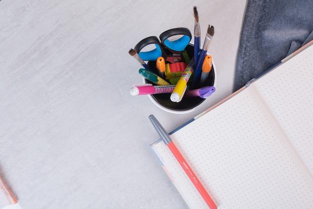 Tesouras, pincéis e lápis em porta-canetas e caderno aberto
