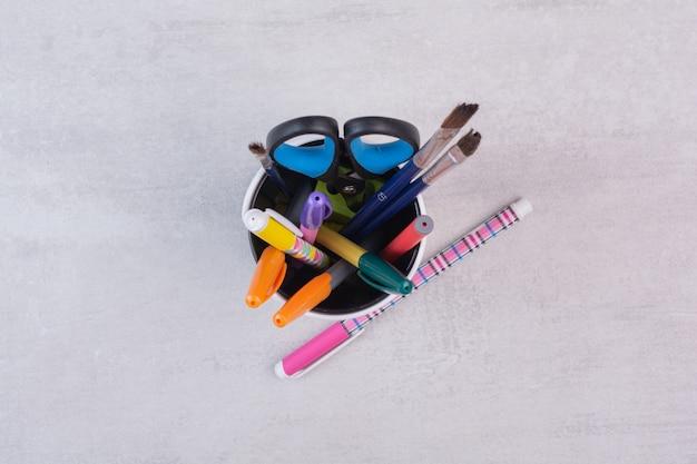 Tesouras, pincéis e lápis no porta-canetas