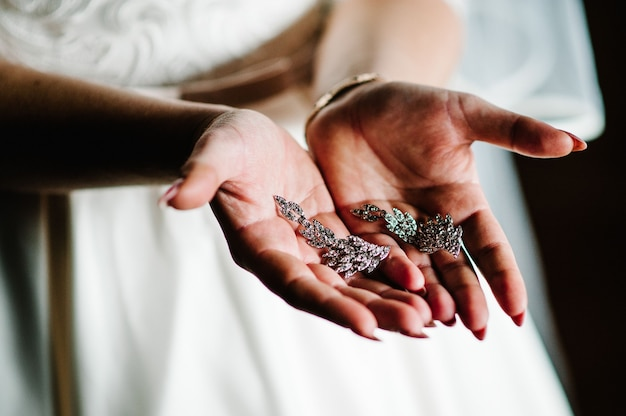Tesouros femininos brinco nas mãos femininas
