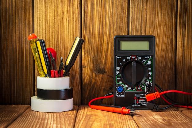 Testador elétrico e kit de ferramentas eletrônicas na mesa de madeira