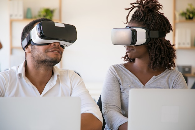 Testadores afro-americanos animados usando óculos de realidade virtual no escritório