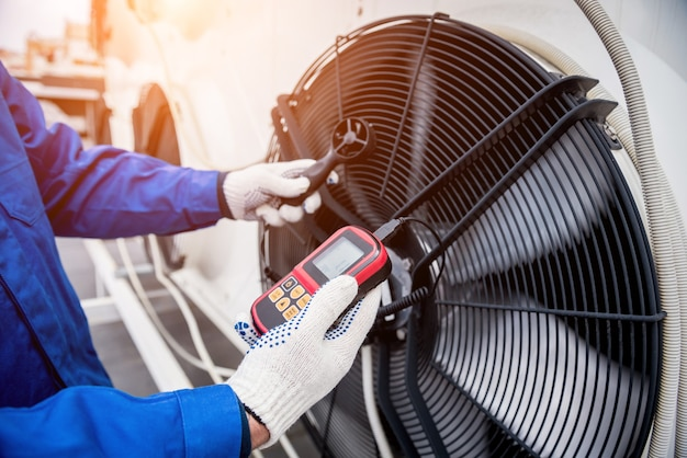 Testando com um anemômetro de um ventilador axial da unidade condensadora
