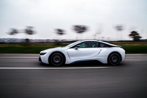Teste de alta velocidade de condução de um carro esporte branco.