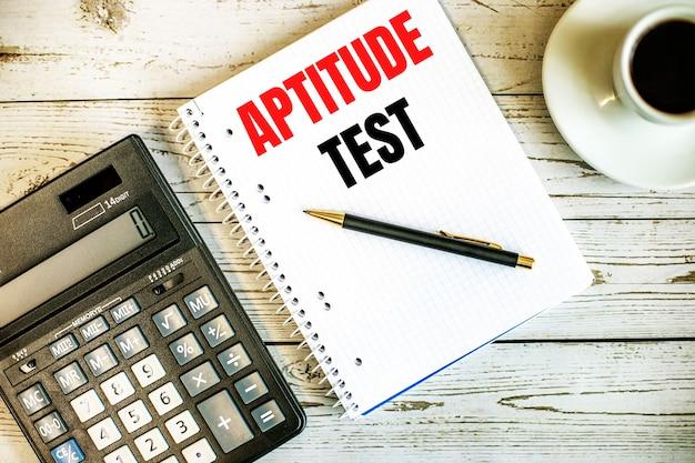 Teste de aptitude escrito em papel branco perto do café e da calculadora em uma mesa de madeira clara