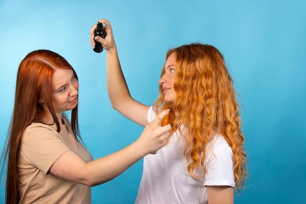 Teste de aroma. meninas de cabelos longos e ruivos borrifam perfume umas nas outras. foto na parede azul.