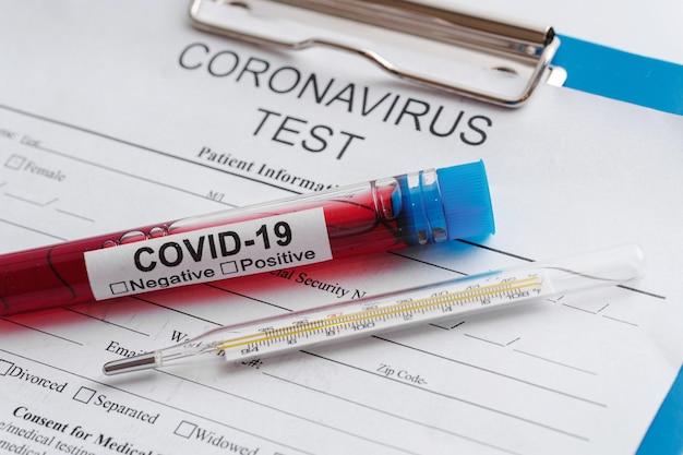 Teste de coronavírus. close da amostra de sangue e termômetro