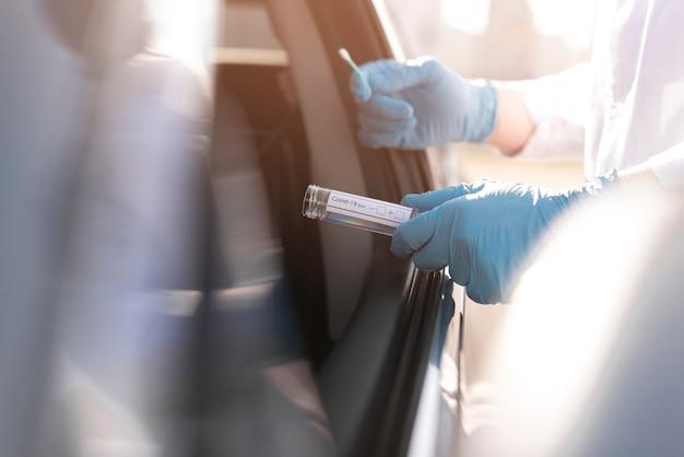 Teste de coronavírus e pessoa usando luvas ao lado de um carro