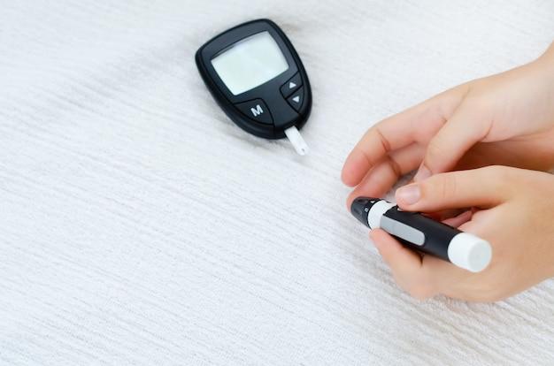 Teste de diabetes e glicemia para teste de açúcar no sangue em crianças com punção de lanceta no dedo