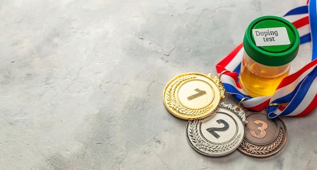 Teste de doping. medalha de ouro, prata e bronze e frasco para análise de urina em fundo cinza.