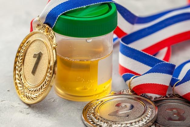 Teste de doping. medalha de ouro, prata e bronze e frasco para análise de urina em superfície cinza.