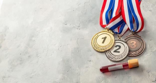 Teste de doping. medalha de ouro, prata e bronze e tubo de ensaio com sangue em fundo cinza.