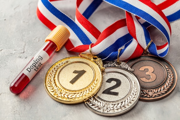 Teste de doping. medalha de ouro, prata e bronze e tubo de ensaio com sangue em superfície cinza.