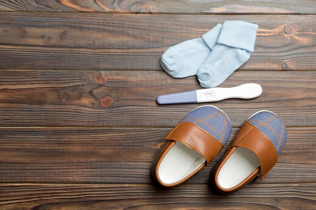 Teste de gravidez com resultado positivo e roupas para recém-nascido, copie o espaço para texto. estendendo a vista superior do conceito de família na mesa de madeira