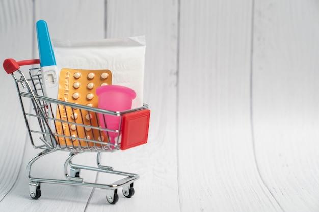 Teste de gravidez, pílula anticoncepcional e absorvente higiênico no carrinho de compras. conceito de contraceptivo.