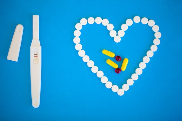 Teste de gravidez positivo com duas listras e pílula anticoncepcional em azul