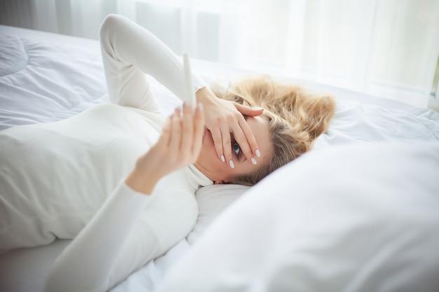 Teste de gravidez positivo, mulher jovem, sentindo-se deprimido e triste depois de olhar para o resultado do teste de gravidez em casa