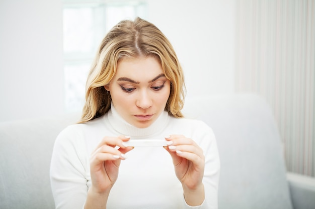 Teste de gravidez. preocupado mulher triste olhando para um teste de gravidez após o resultado