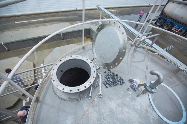 Teste de metanol químico do tanque de aço inoxidável com tampa aberta de bueiro no tanque de bueiro frontal confinado em aço inoxidável.