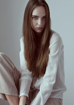 Teste de modelo com a jovem e bela modelo com cabelos longos, vestindo camisa branca em fundo cinza